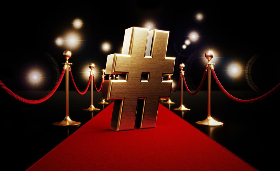 Gold Hashtag Symbol Standing on Red Carpet and Paparazzi Lights on Black Background