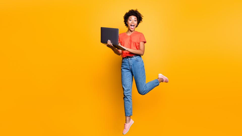 Full size photo of amazed crazy curly brown hair girl use her laptop have notification in feednews jump scream omg wear denim jeans red t-shirt lifestyle sneakers isolated yellow color background