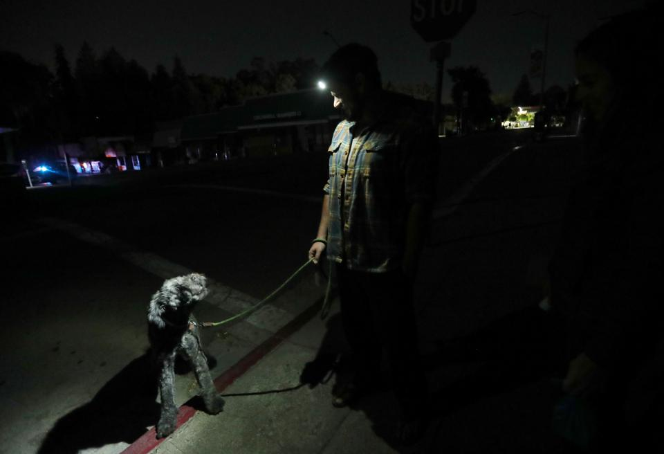 Tony and Lauren Scherba walk their dog Gandalph minutes after the power went out in Oakland, California on October 9.