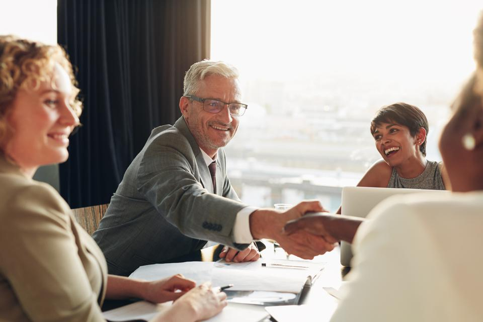 Smiling businessman shaking hands with a colleague during a meeting