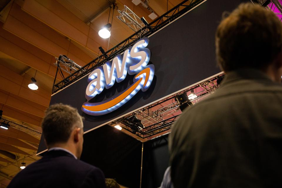People pass by AWS (Amazon Web Services) stand during the...