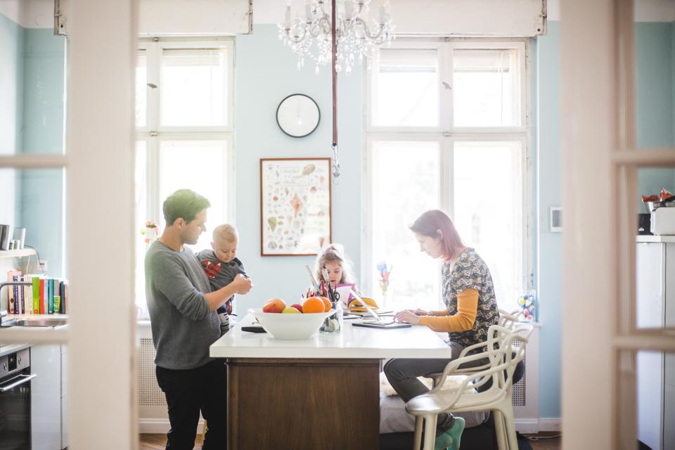Father playing with son while standing by girl and woman busy at kitchen island