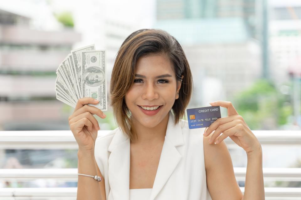 Successful beautiful Asian business  woman holding money US dollar bills and credit card in hand , business concept