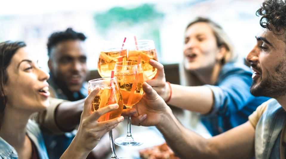 Friends drinking spritz at fashion cocktail bar restaurant - Friendship concept with young people having fun together toasting drinks on happy hour at pub - Focus on central glass - Teal orange filter