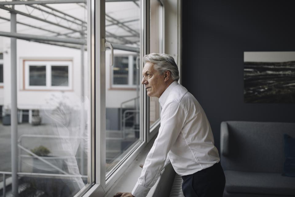 Senior businessman looking out of the window