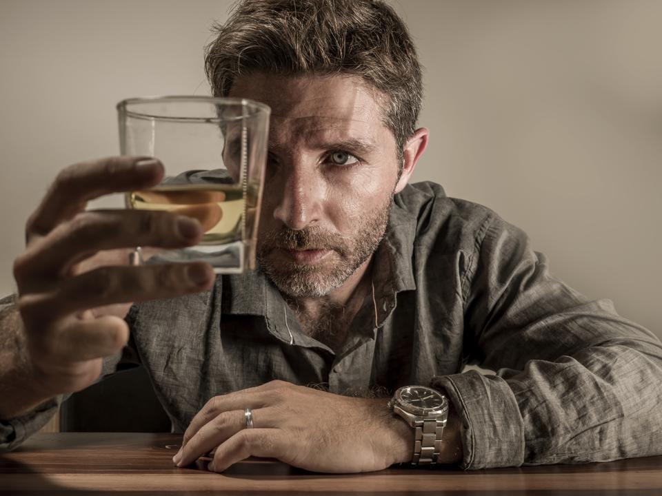 alcoholic depressed and wasted addict man sitting in front of whiskey glass trying holding on drinking in dramatic expression suffering alcoholism and alcohol addiction isolated on grey background