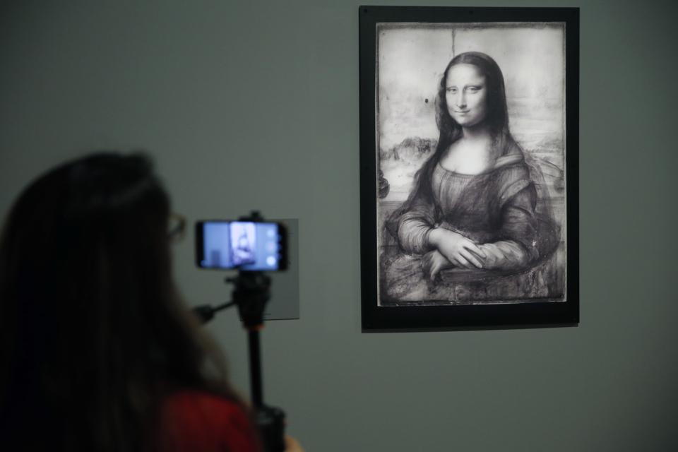 A visitor takes a picture of an infrared reflectography of the painting Mona Lisa by the Italian Renaissance artist, Leonardo da Vinci.