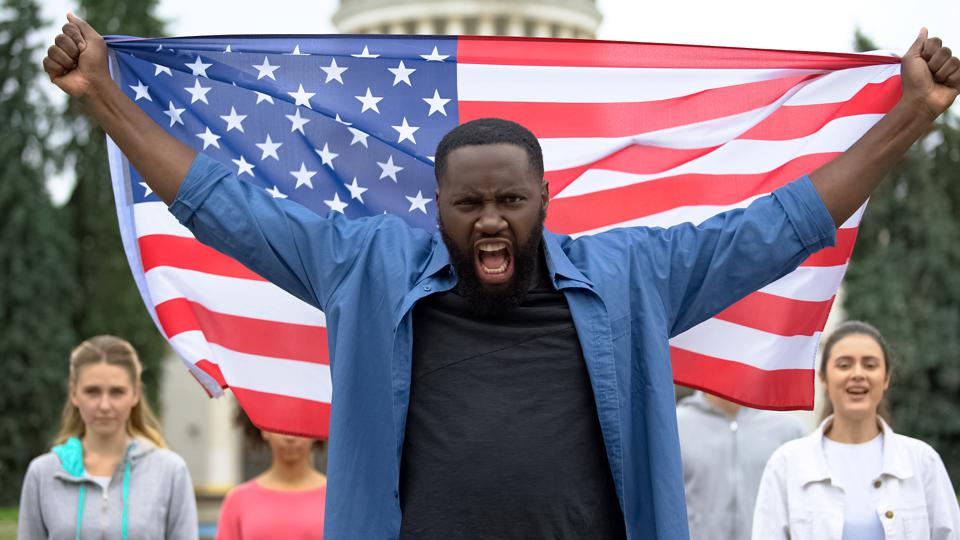 Irritated black man raising American flag, anti-racist rally, US migrant crisis