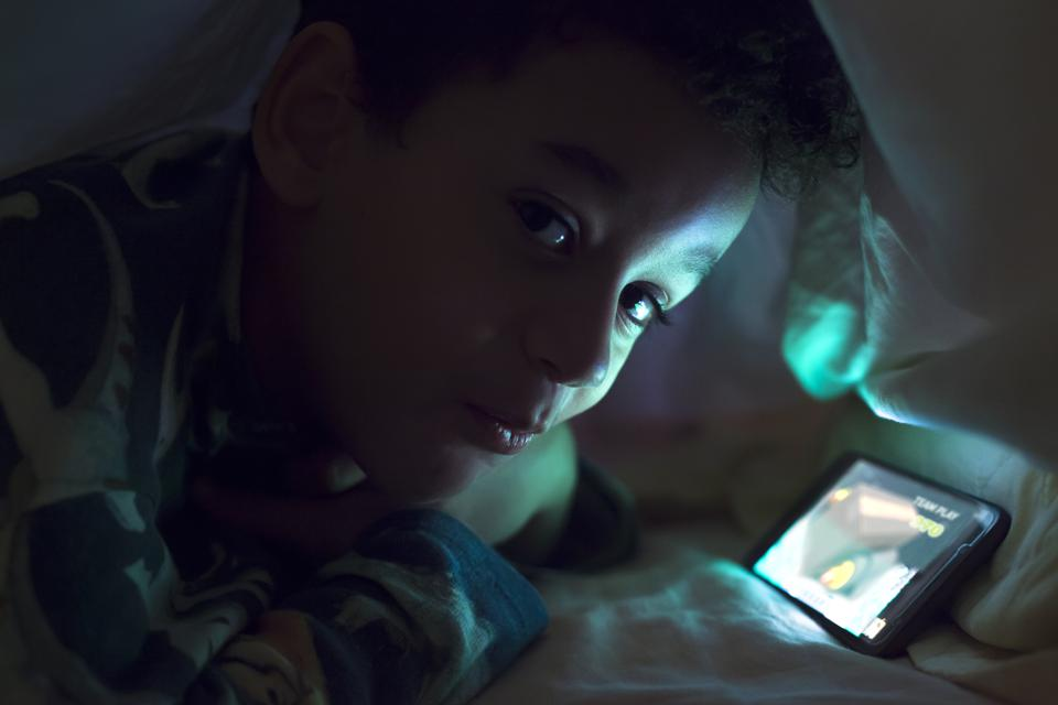 smart boy playing with smartphone hidden under the duvet