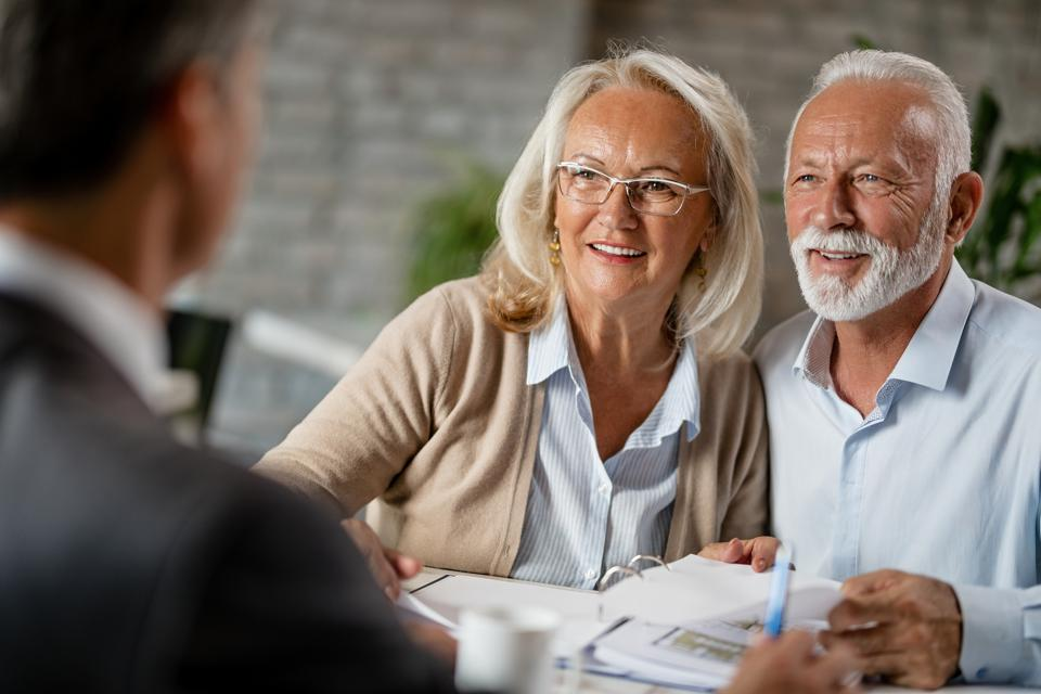 Happy senior couple having a meeting with real estate agent.