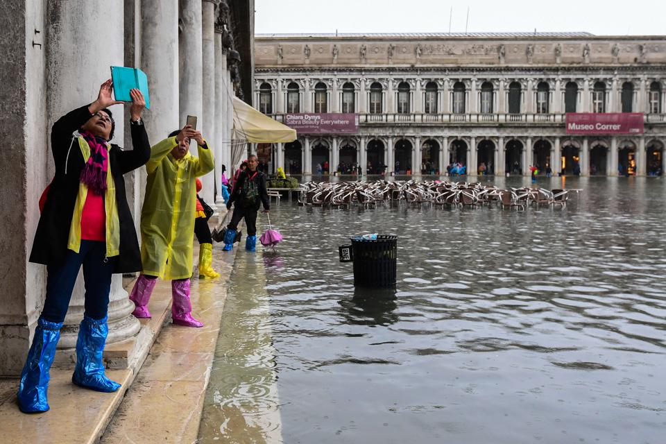 Tourists at a flooded St. Mark's Square, Venice