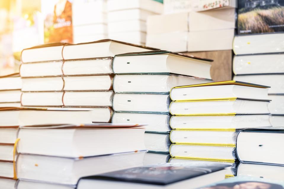 Étagère de librairie avec pile de nouveaux livres avec assiette vide rouge.  Nouveaux arrivages à la librairie.  Présentation du livre.  Copyspace