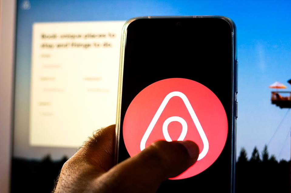 In this photo illustration the Airbnb logo is displayed on a...