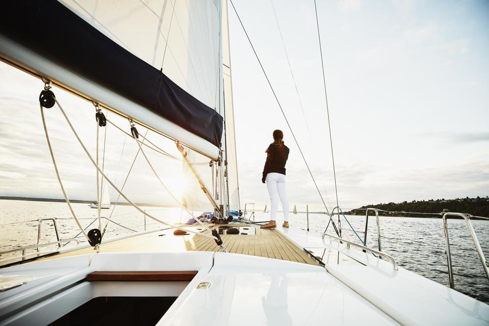 Female sailor standing on foredeck of sailboat watching sunset on summer evening