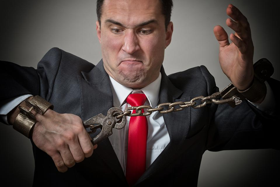 Businessman with chained hands