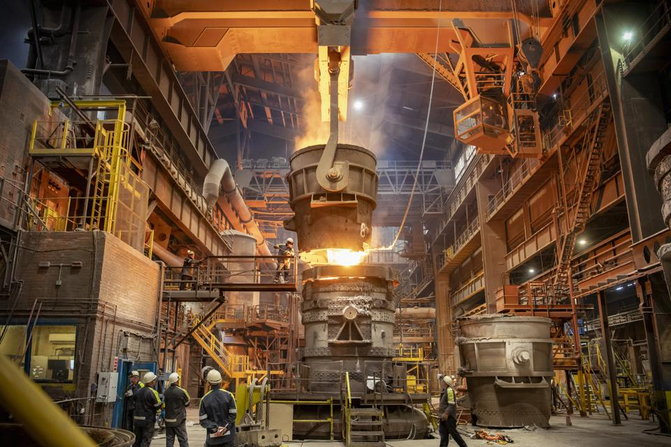 Steelworkers looking on during steel pour in steelworks