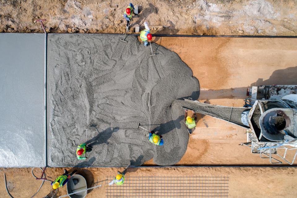 A construction worker pouring a wet concrete at a road construction site
