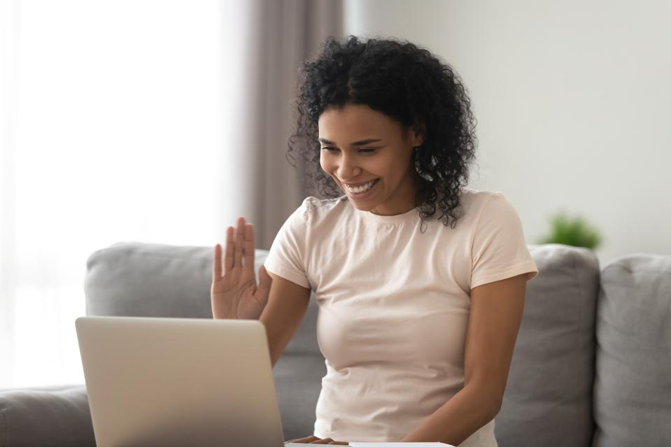 Woman sitting on couch looking at computer screen wave hand