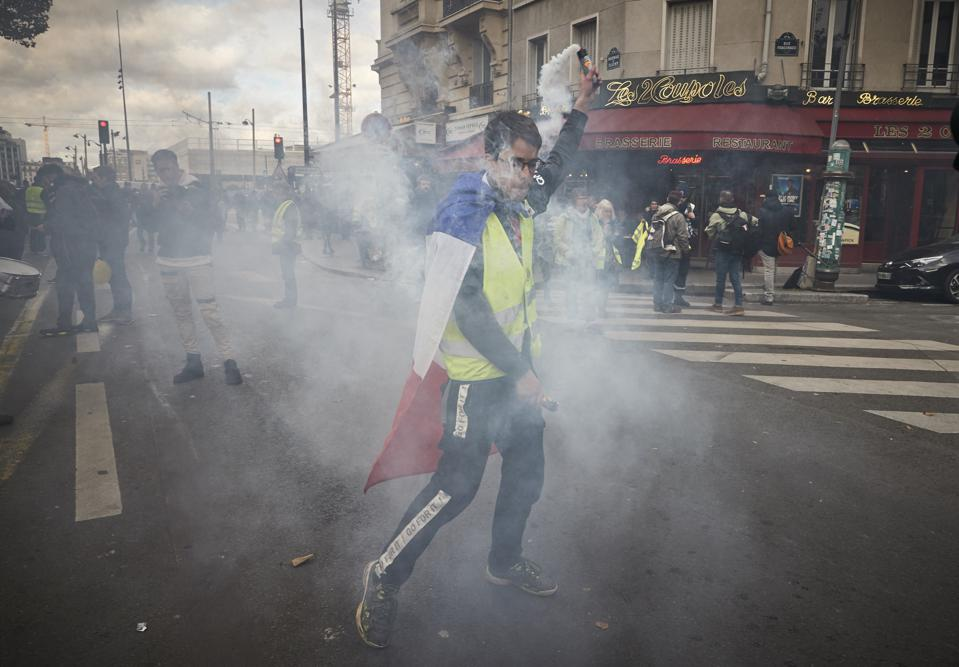 A yellow vest protestor waves a flare as demonstrators march through Paris during Act 52 of protests in Paris