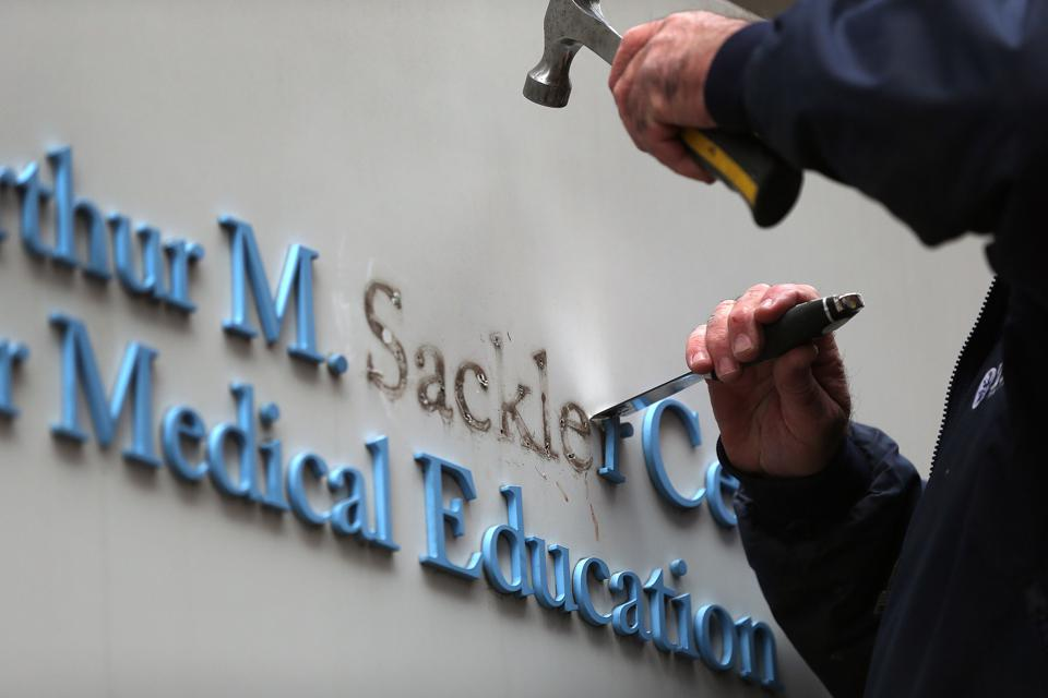 A Tufts University employee removes letters from signage featuring the Sackler family name.