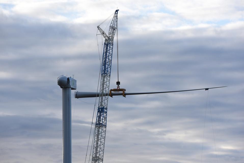 Mechanical cranes lift the blade of a wind turbine near the...