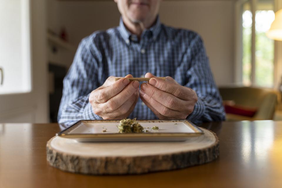 Senior man at home rolling marihuana joint