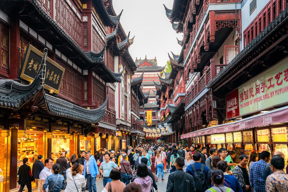 Local and tourists enjoying Shanghai's famous traditional architecture of yuyuan garden in evening at warm summer day in downtown Shanghai in China, Asia.