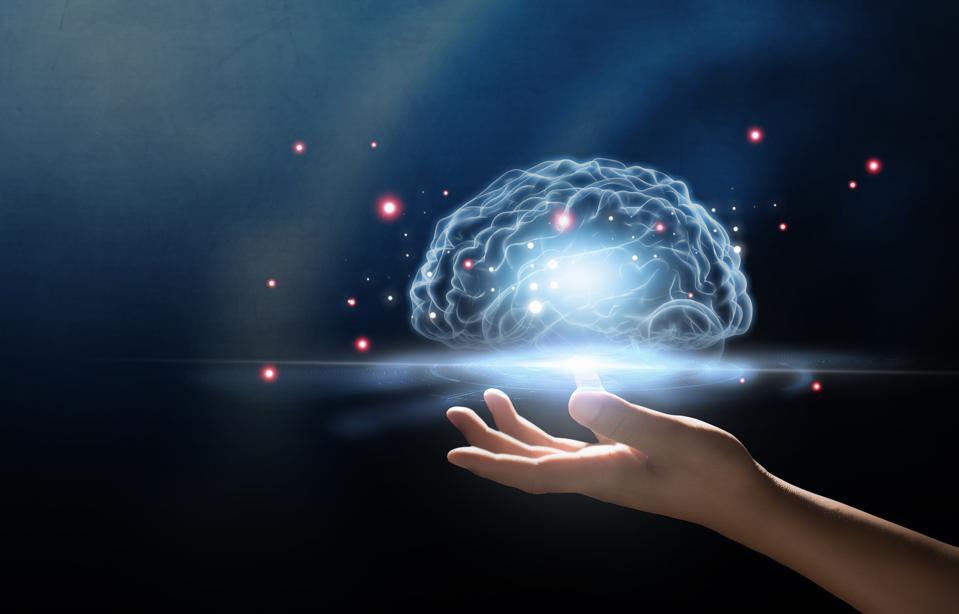 Digital Composite Image Of Hand Holding Illuminated Digital Brain Mid-Air Against Black Background