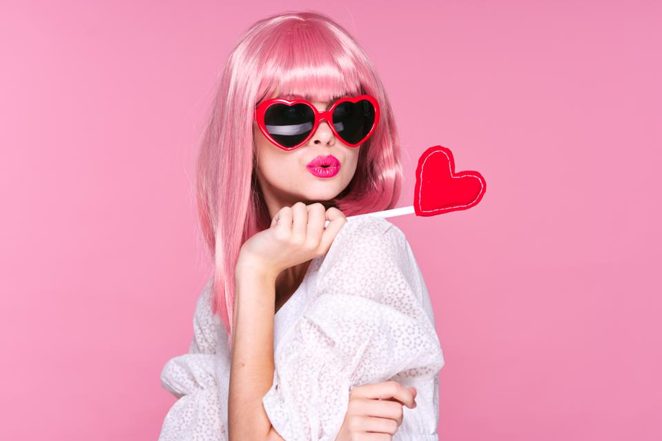 Woman with heart in hand, Valentine's day, glasses hearts and pink background
