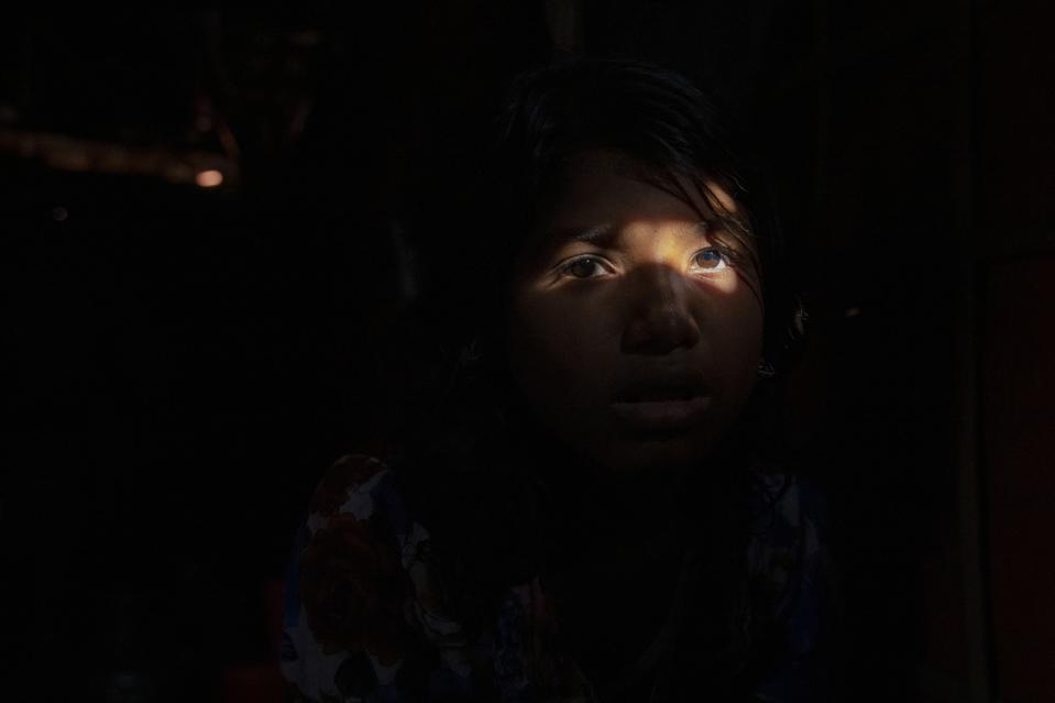 Portrait of a Rohingya girl siting in her makeshift tent at...