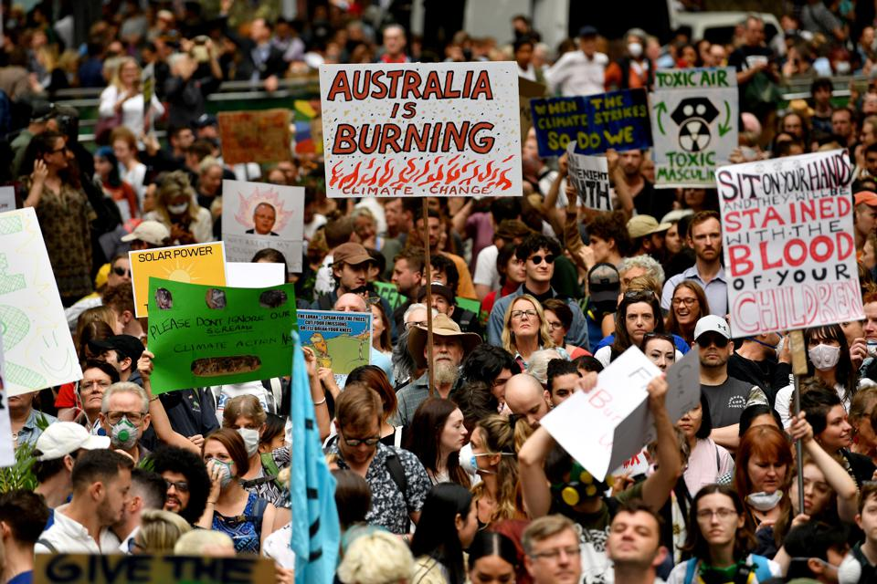Demonstrators raise placards at a climate protest rally in Sydney on December 11.