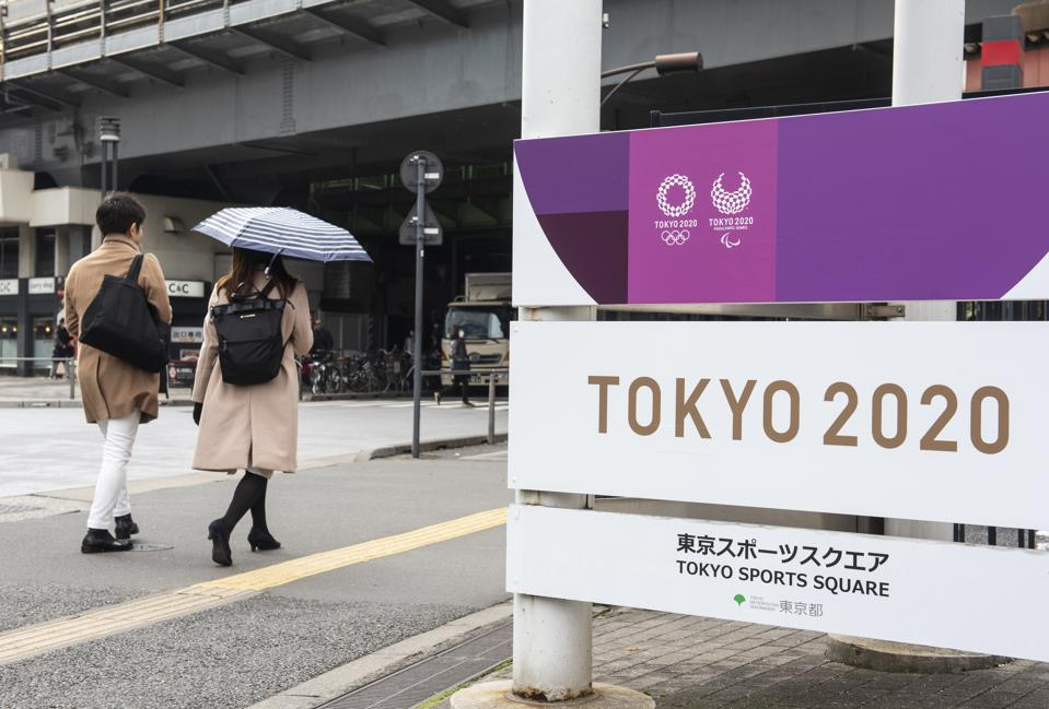 Commuters walk past a sign promoting the upcoming 2020 Tokyo...