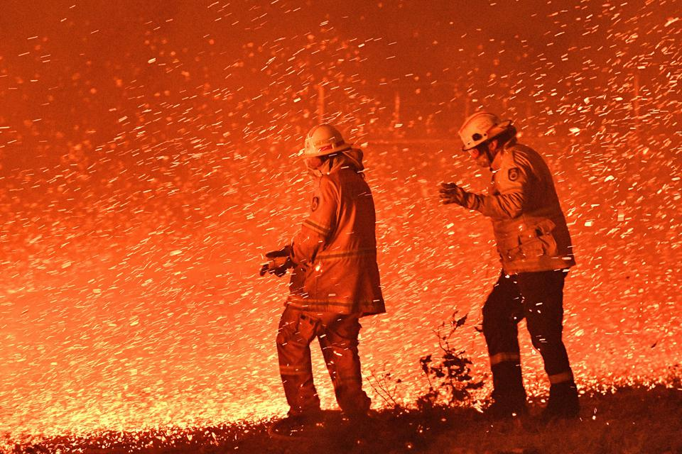 Firefighters near the town of Nowra in New South Wales struggle against strong wind in an effort to secure nearby houses.