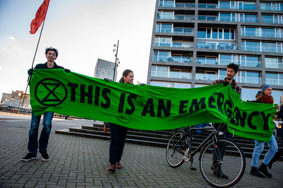 Extinction rebellion activists hold a  green banner during...