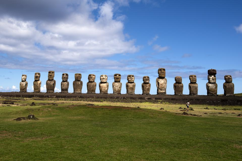 A tourist in front of group of Moai statue of Ahu Tongariki, Easter Island, Chile
