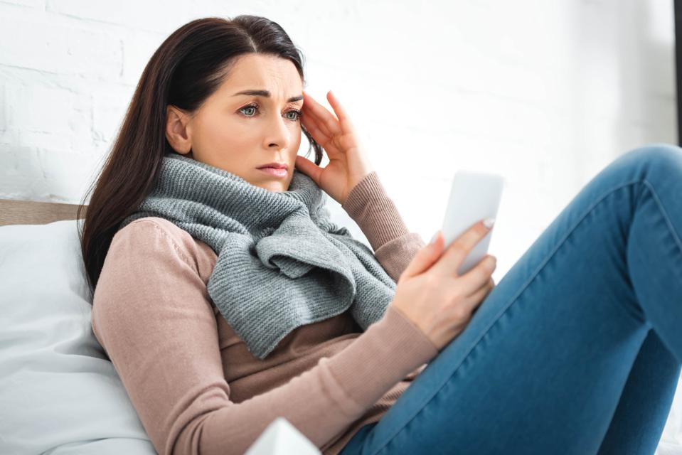 Tired ill woman having online consultation with doctor.