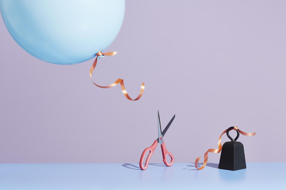 A pair of scissors cutting a balloon string to release the balloon