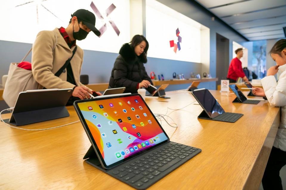 Los clientes admiran los productos iPad Pro en una tienda minorista de Apple ...