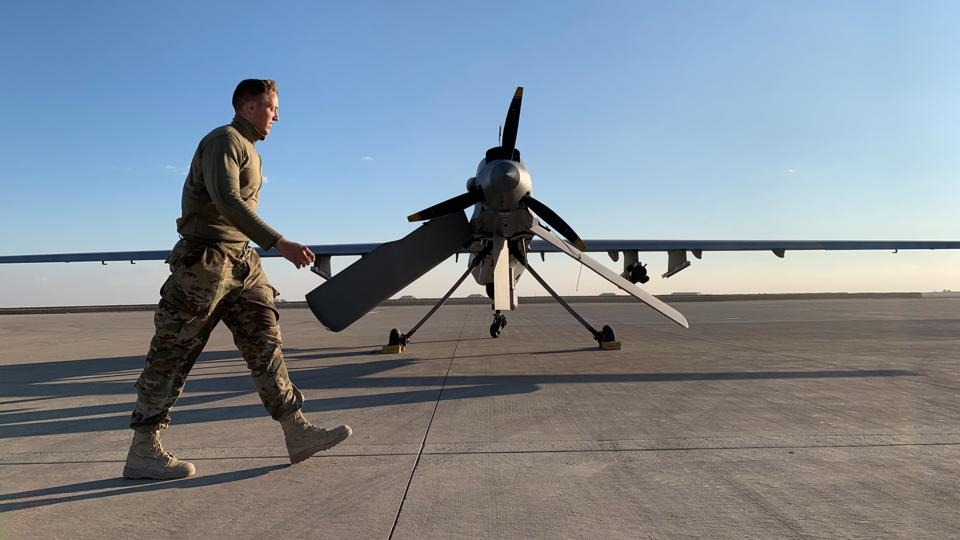 A U.S. service member walks past a drone on the Ayn al-Asad airbase in Iraq, where American troops work in coalition against ISIS.