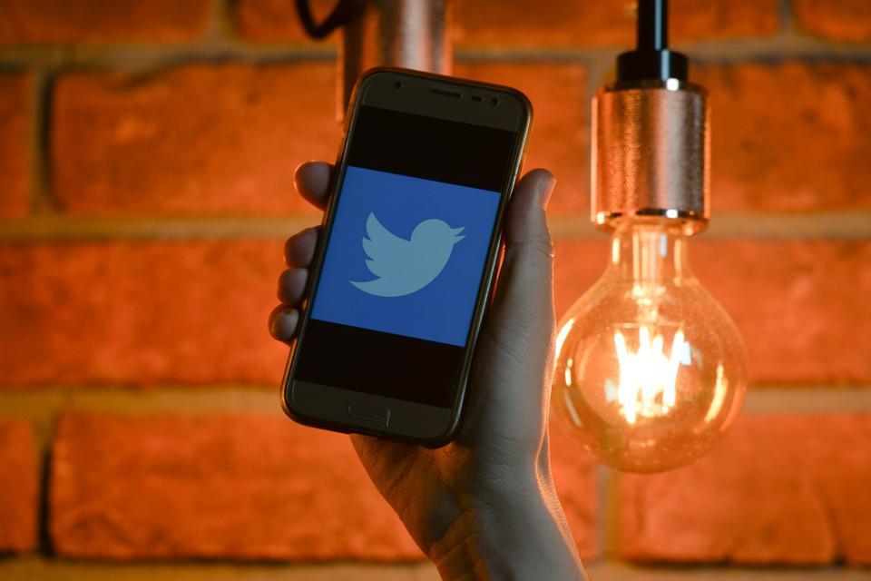 Twitter logo on mobile phone screen.