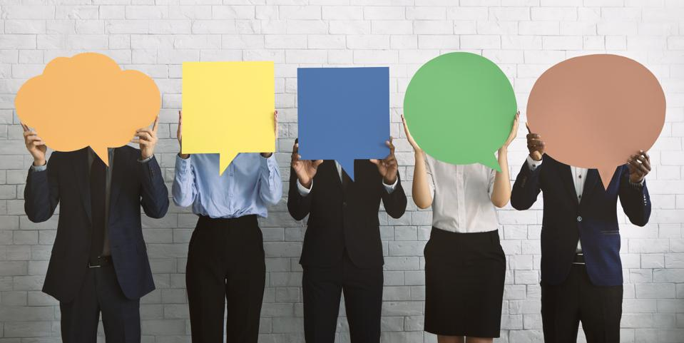 Group of people hiding faces behind different shaped and colored speech bubbles