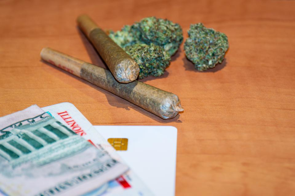 Recreational cannabis in Illinois. Two marijuana joints and State ID card.