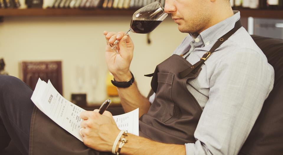 Close-up, sommelier tasting red wine and making notes. Profession in winemaking.