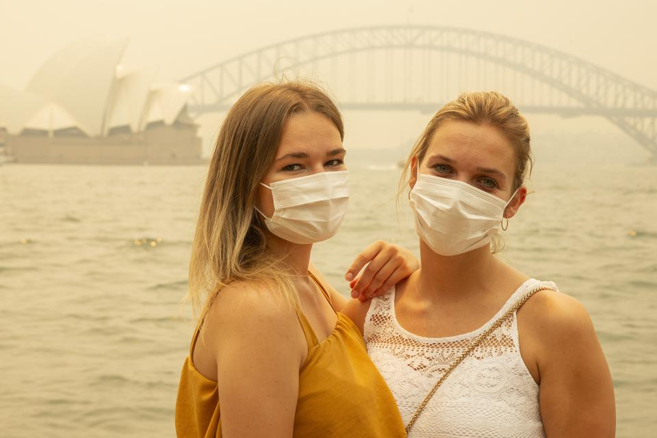 German tourists Julia Wasmiller, left, and Jessica Pryor pose for a photo while wearing face masks December 19 in Sydney.