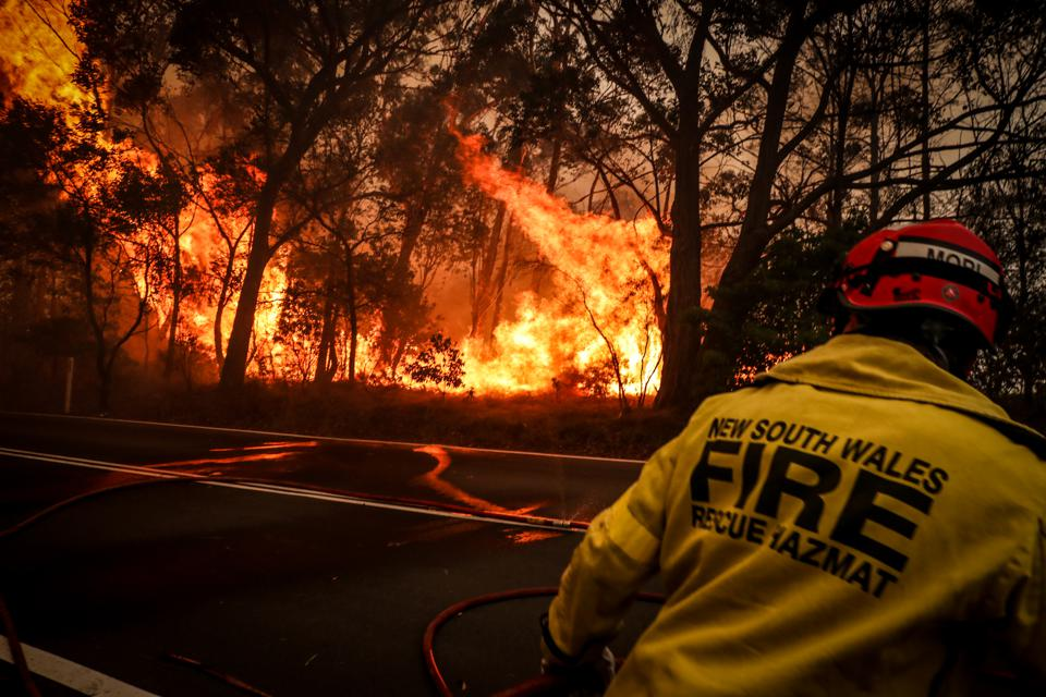 A firefighter run from a bushfire burning on the outskirts of the town of Bilpin on December 19 in Sydney, Australia.