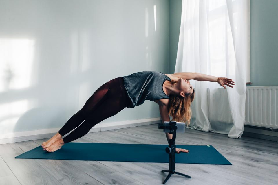 Woman Stretching Over Exercise Mat While Filming Through Phone On Tripod For Vlogging At Home