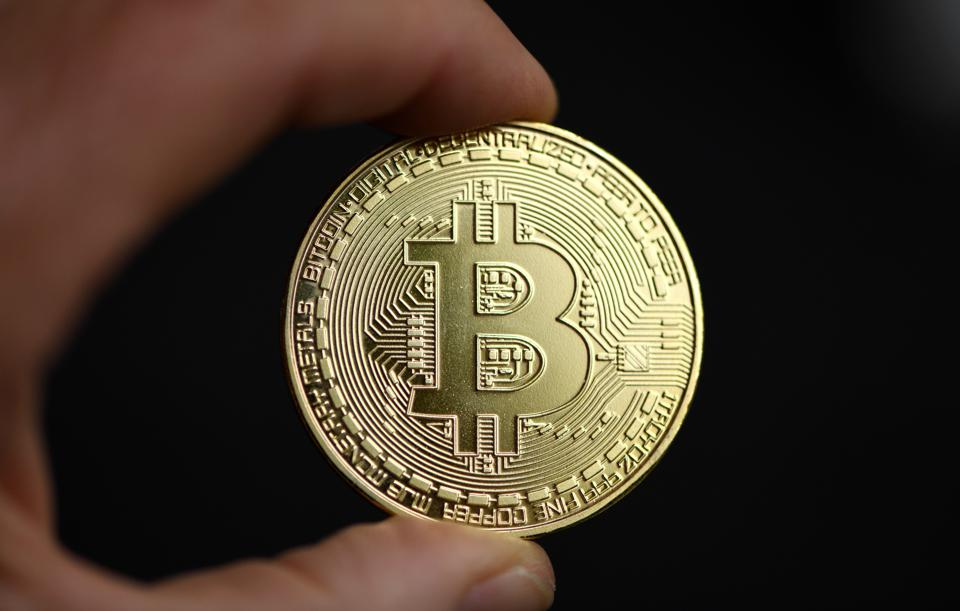 Bitcoin, a cryptocurrency, held up against a black background.