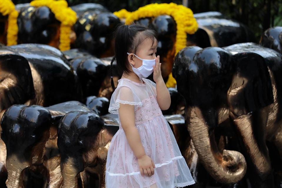 Chinese girl wearing a protective face mask stands near the...