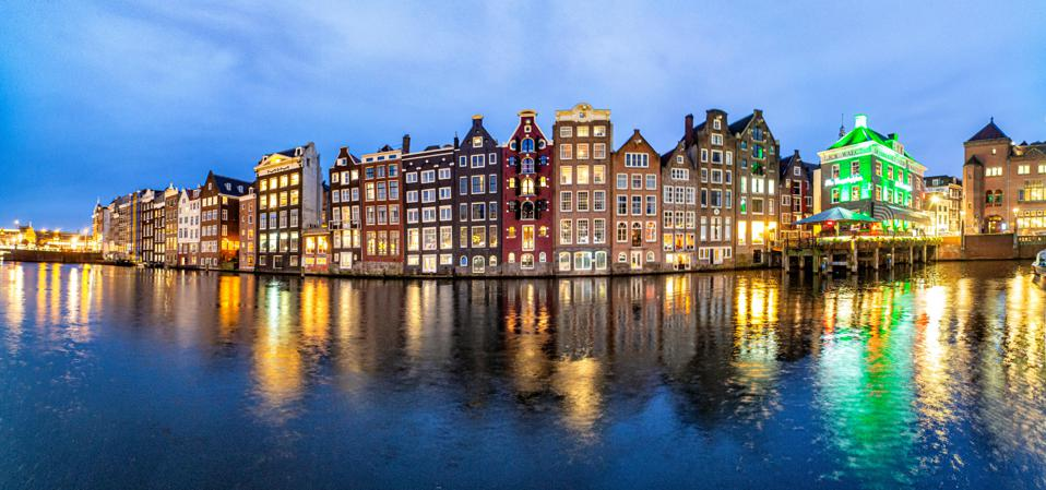 Famous Reclining Houses At Damrak Canal In Amsterdam
