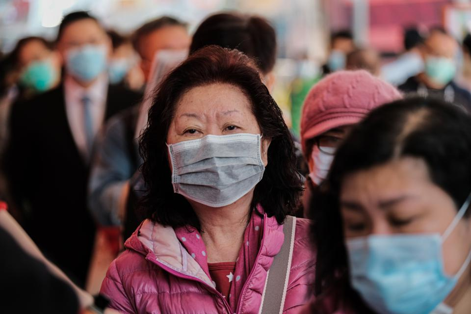 A lady seen in her mask as hundreds of people wait in a...